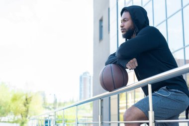 side view of pensive african american man leaning at railings with basketball ball and looking away