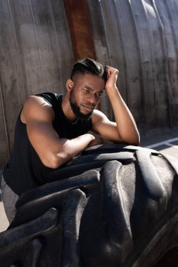 pensive african american sportsman leaning at tyre and looking away on street