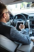 Fotografie partial view of businessman in eyeglasses using tablet in car