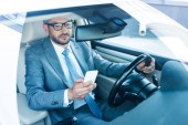 Fotografie portrait of businessman with smartphone driving car