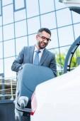 portrét podnikatele v brýlích uvedení zavazadla do auta na parkovišti