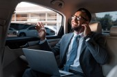 Fotografie businessman in earphones with laptop listening music in car