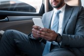 Fotografie partial view of businessman using smartphone while sitting on backseat in car