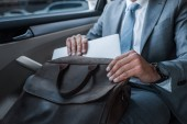 Fotografie cropped shot of businessman in suit putting papers into bag while sitting on backseat in car