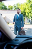 businessman in suit and eyeglasses with car keys going to car on street