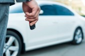partial view of businessman with car keys in hand and car on background