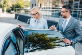 Fotografie portrait of businessman helping colleague sit into car on street