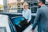 businessman opening car door for colleague on parking