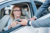 Fotografie partial view of businessman giving car keys to smiling colleague at driver seat in car