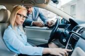 Geschäftsmann berät Geschäftsfrau im Auto