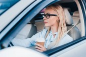 side view of blonde businesswoman with coffee to go driving car