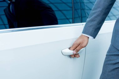 cropped shot of businessman opening car door on street