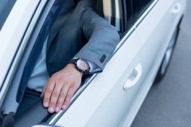 cropped shot of businessman sitting at drivers seat in car