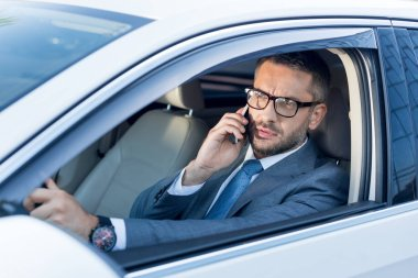 portrait of businessman in eyeglasses talking on smartphone while driving car