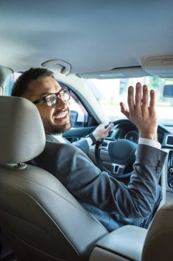smiling businessman in suit and eyeglasses greeting someone while driving car
