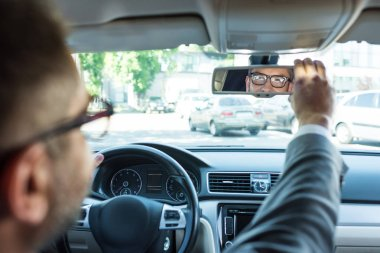 partial view of businessman in eyeglasses looking at rear view mirror in car
