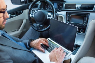 businessman in eyeglasses using laptop with blank screen in car