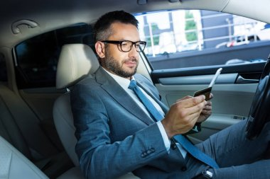 side view of businessman with tablet and credit card sitting in car