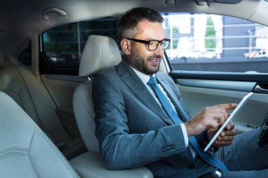 side view of smiling businessman in eyeglasses using tablet in car