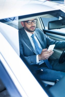 portrait of businessman with smartphone driving car
