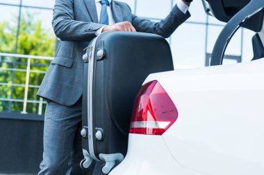 partial view of businessman putting luggage into car on parking