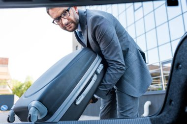 portrait of businessman in eyeglasses putting luggage into car on parking