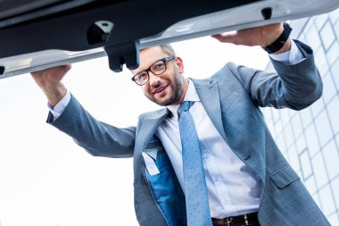 businessman in suit and eyeglasses looking into car luggage boot