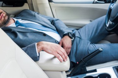 cropped shot of tired businessman sleeping in car
