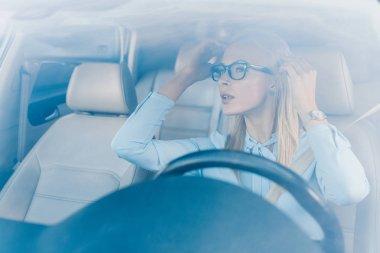blonde businesswoman in eyeglasses looking at rear view mirror in car