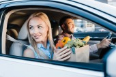 Fotografie selective focus of married couple with paper bag full of healthy food in car