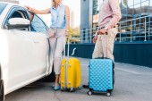 Fotografie partial view of husband and wife with baggage standing at car on parking
