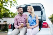 Fotografie portrait of smiling couple with coffee to go sitting on car and looking at each other