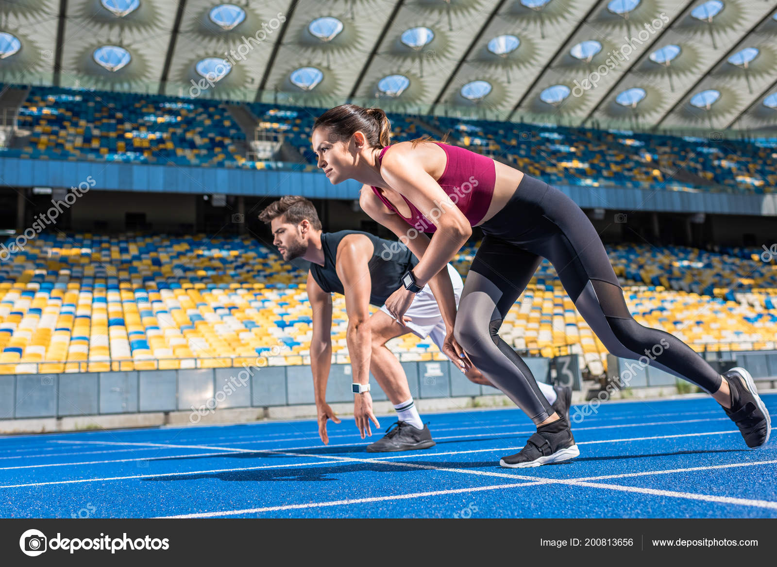 athletic young male female sprinters start position running track