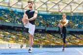 Junges Sportlerpaar wärmt Beine vor dem Joggen auf Laufstrecke am Sportstadion