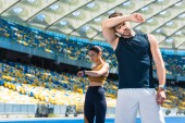 Fotografie exhausted couple standing on running track at sports stadium after jogging