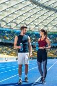 Fotografie junges sportliches Paar mit Flaschen Wasser stehend auf der Laufstrecke am Sportstadion und reden