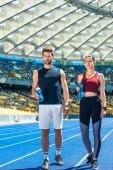 Fotografie junges sportliches Paar mit Flaschen Wasser stehen auf Laufstrecke am Sportstadion