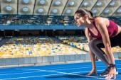 athletic female runner in start position on running track at sports stadium