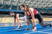 Fotografie sportliche Junge männliche und weibliche Sprinter in Startposition auf Laufstrecke am Sportstadion