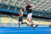 Fotografia motion shot of young male and female joggers running on track at sports stadium
