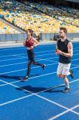 Fotografia attraente giovane jogging maschio e femmina di correre sulla pista allo stadio di sport
