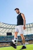 handsome young soccer player exercising with ball at sports stadium