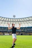 Sportive mladý fotbalista skákací míč na hlavu na sportovní stadion