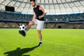 athletic young soccer player bouncing ball on leg at sports stadium