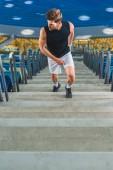 Fotografie cropped shot of sportsman jogging upstairs at sports stadium
