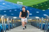 Fotografia vista di alto angolo di giovane uomo attraente al piano di sopra a fare jogging a stadio sportivo