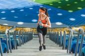 Fotografia vista di alto angolo di giovane donna attraente al piano di sopra a fare jogging a stadio sportivo