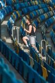 Fotografia vista laterale di giovane uomo attraente al piano di sopra a fare jogging a stadio sportivo