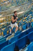 Fotografia attraente giovane jogging sopra allo stadio di sport