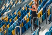 Fotografie cropped shot of beautiful young woman standing on tribunes at sports stadium